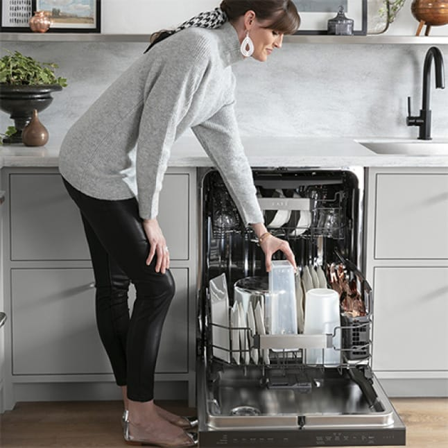 A woman leans down to place a dirty plastic food storage bin into the lower rack of the Dishwasher to be cleaned.