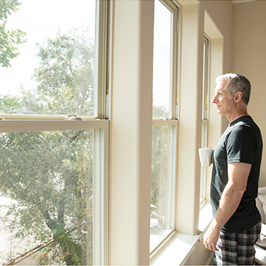 Man standing beside window comfortably drinking coffee