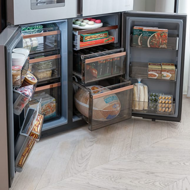 Bottom two refrigerator doors open to reveal a stocked freezer with different shapes and sizes of frozen food items.