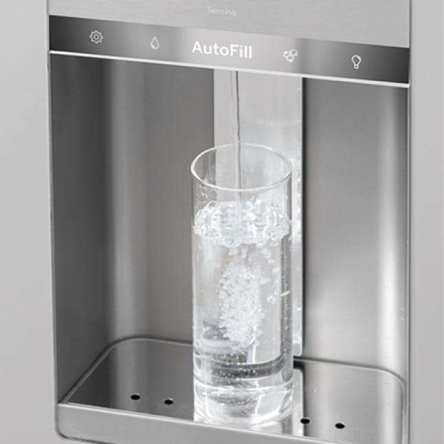 Glass being filled with water in the dispenser tray