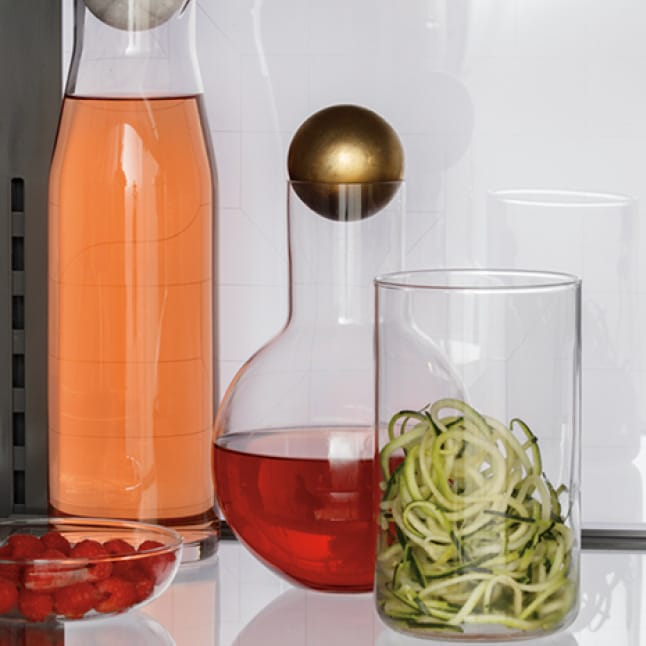 Glass carafes of wine and jars of food illuminated by the back LED lighting.