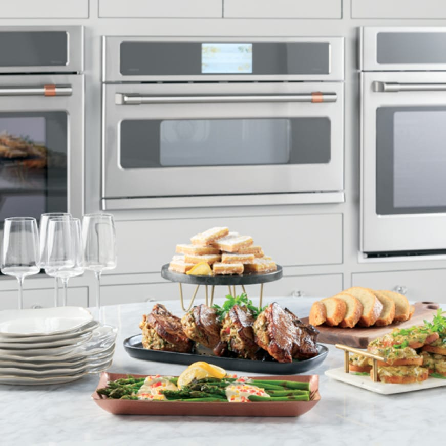 An advantium oven is installed between two wall ovens.A variety of gourmet foods are arranged on a counter in front of the ovens.