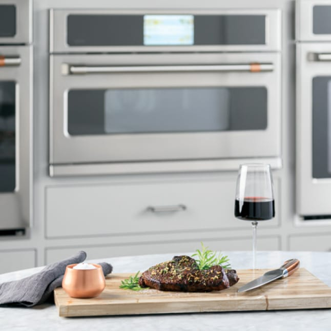 An adaptable advantium oven is installed between two larger wall ovens.A meal on a wooden tray is arranged on a counter in front of the oven.