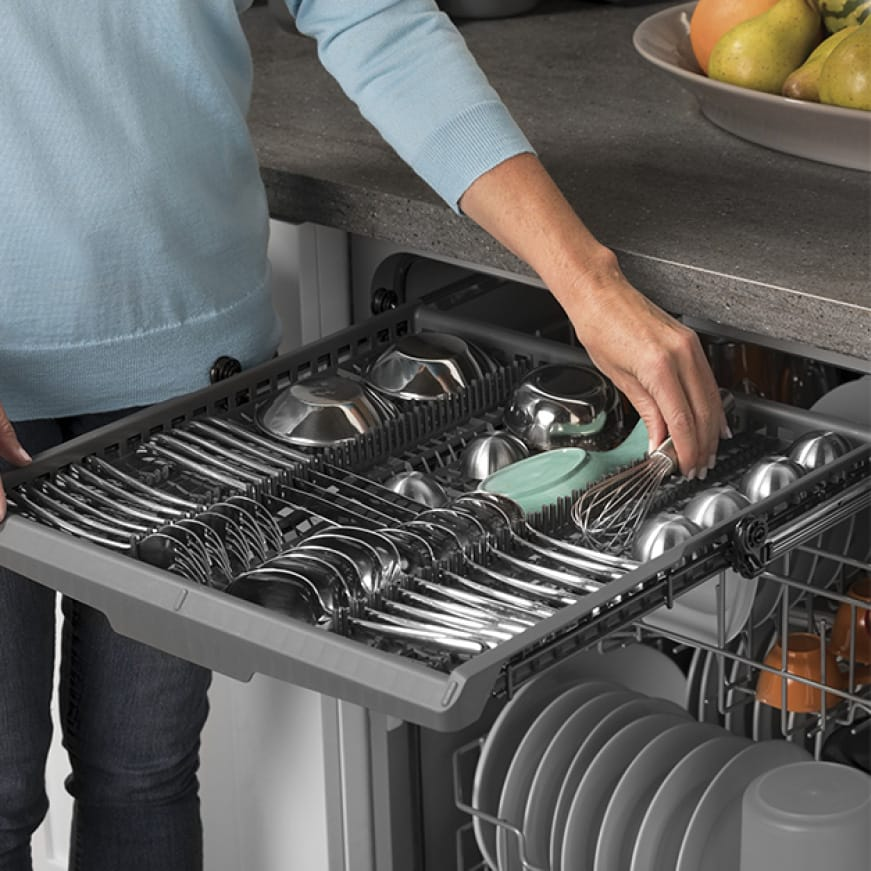 A hand pulls out the upper rack from the top of the dishwasher.Various small cookware and utensils are held by the rack.