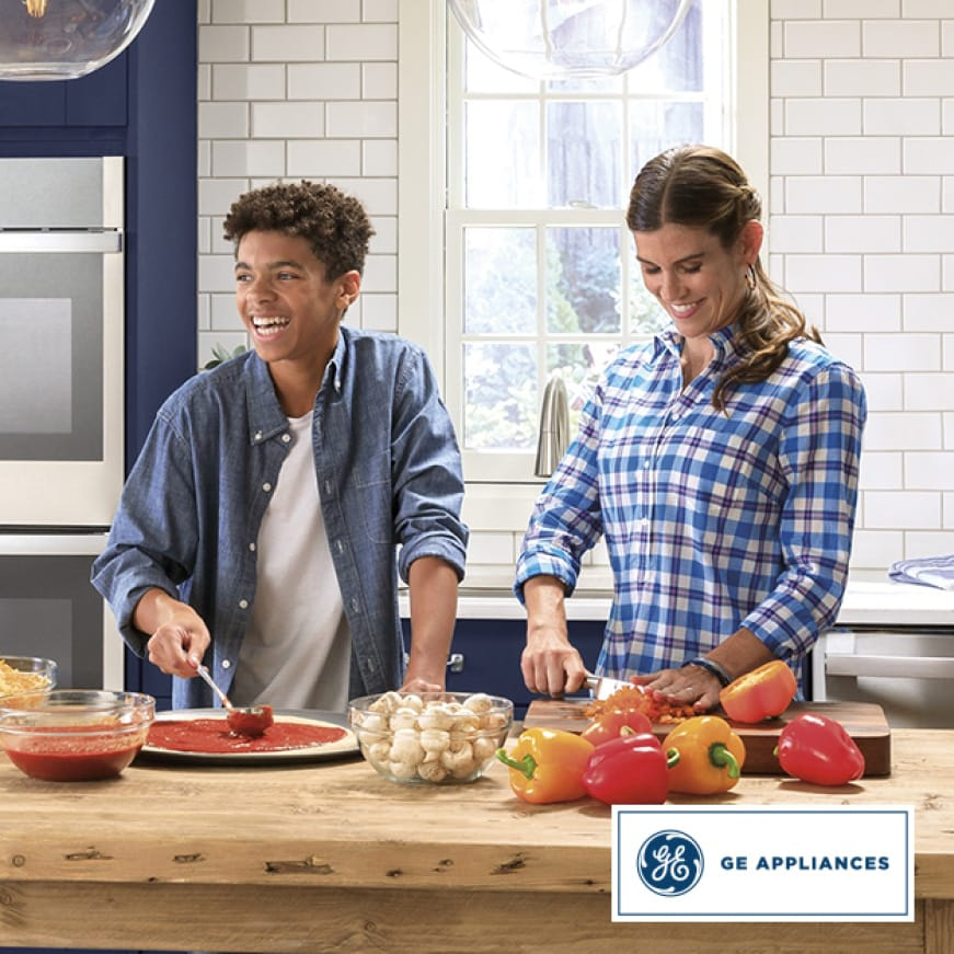 A woman chops peppers while a laughing teenage boy spoons pizza sauce on to a pizza crust.