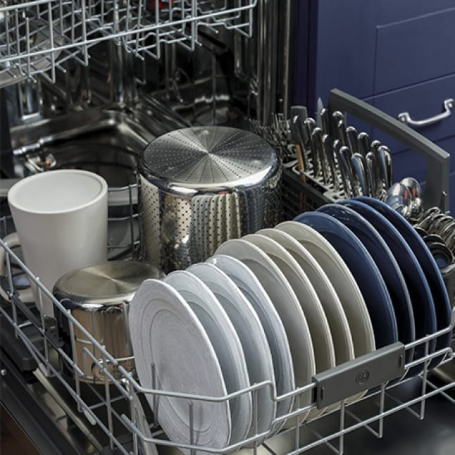 A variety of dishware and cookware has been placed into only the lower rack of the dishwasher