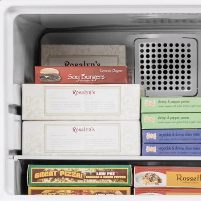 A variety of frozen foods are stacked neatly in the freezer compartment on glass shelves.