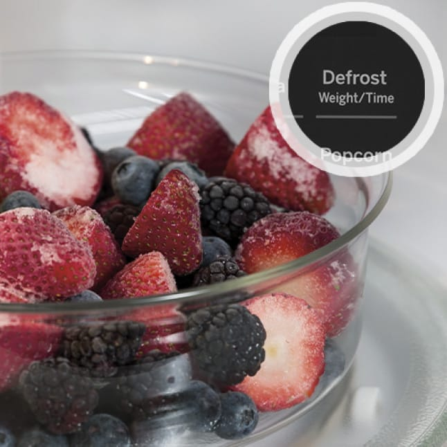 Frozen berries in a glass bowl defrost inside the microwave's cavity.A circular overlay shows the defrost button on the control panel.