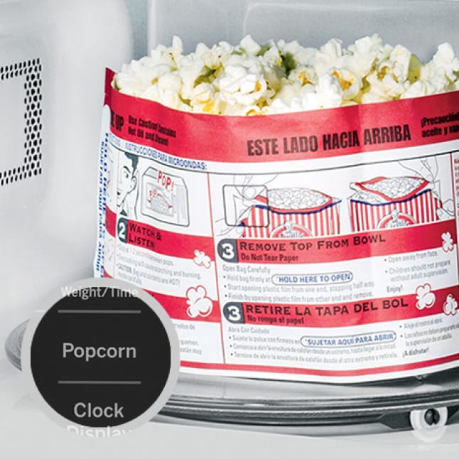 Popcorn cools off in the microwave.A circular overlay shows the popcorn button on the control panel.