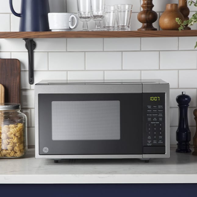 The microwave sits on the countertop underneath a shelf of kitchenware