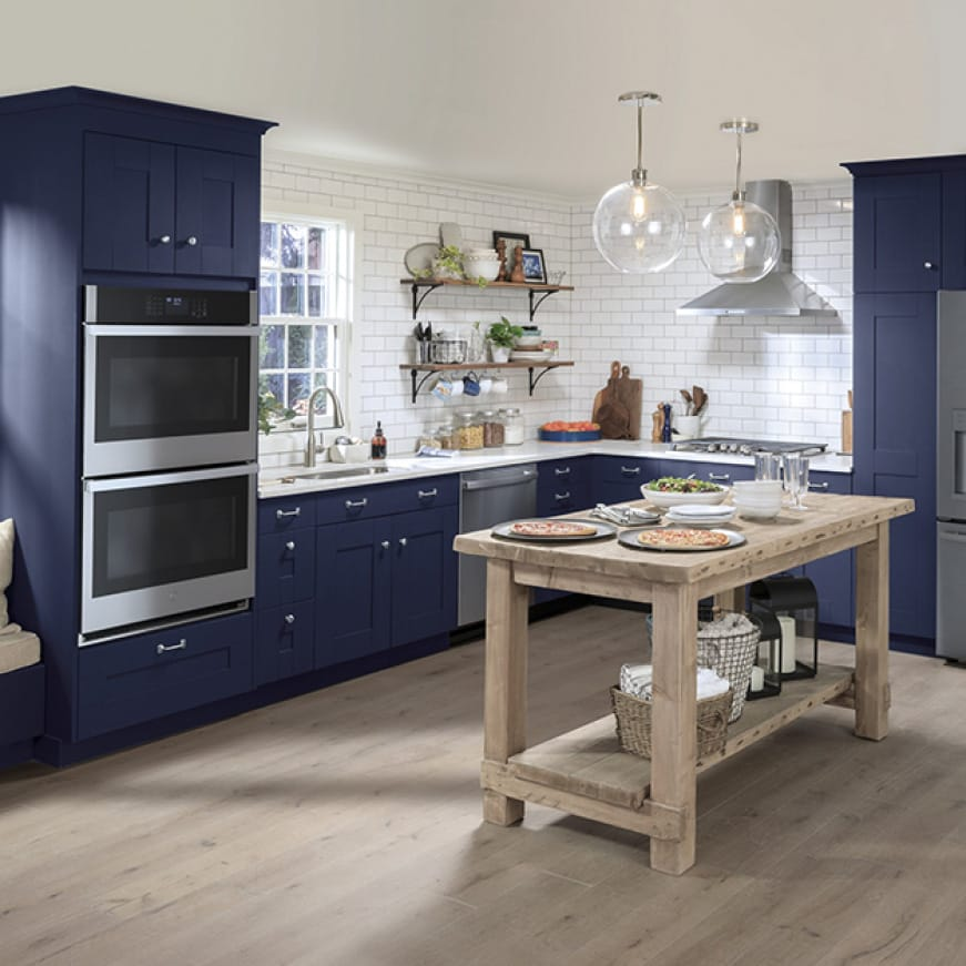 A conservative but stylish kitchen.GE Appliances with a stainless steel finish are installed in simple blue cabinetry.