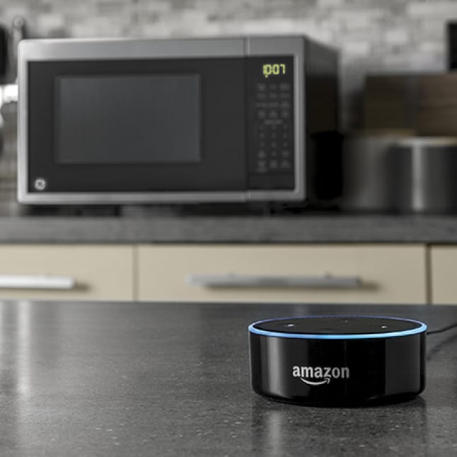 An Amazon Echo sits on a stone countertop with a stainless steel smart home enabled microwave in background