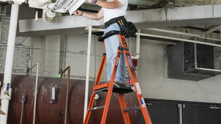 man using podium ladder in garage