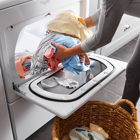 Woman transferring fresh clothes from the dryer to a laundry basket, while the dryer door supports it from below.