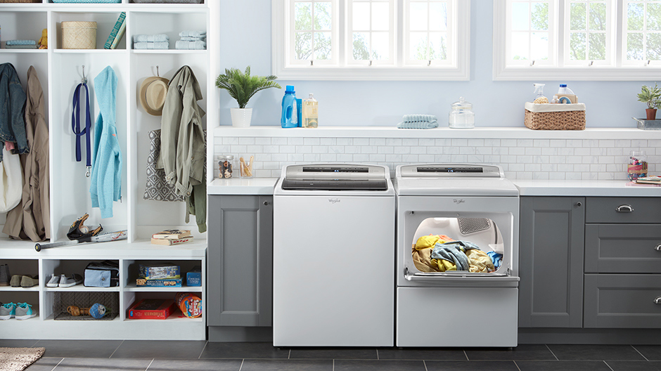White washer and dryer pair set in a modern laundry room. The dryer door is open showing a lit interior and a bright load of dry laundry.