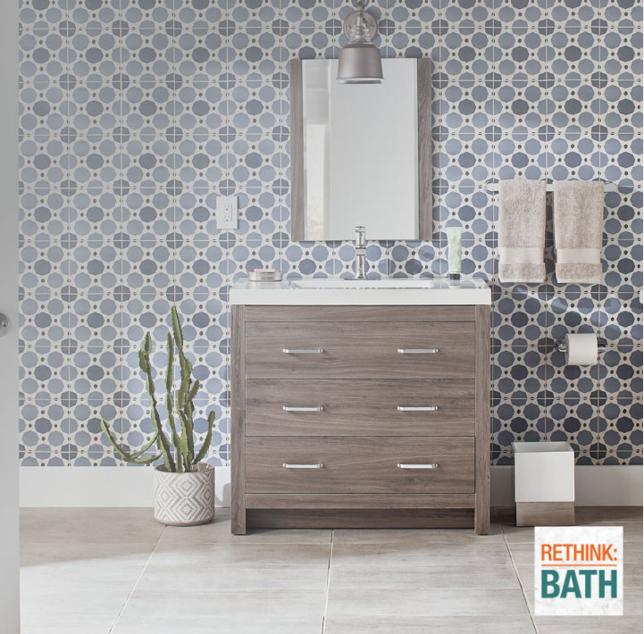 Blue and gray bath tiles behind vanity mirror and light