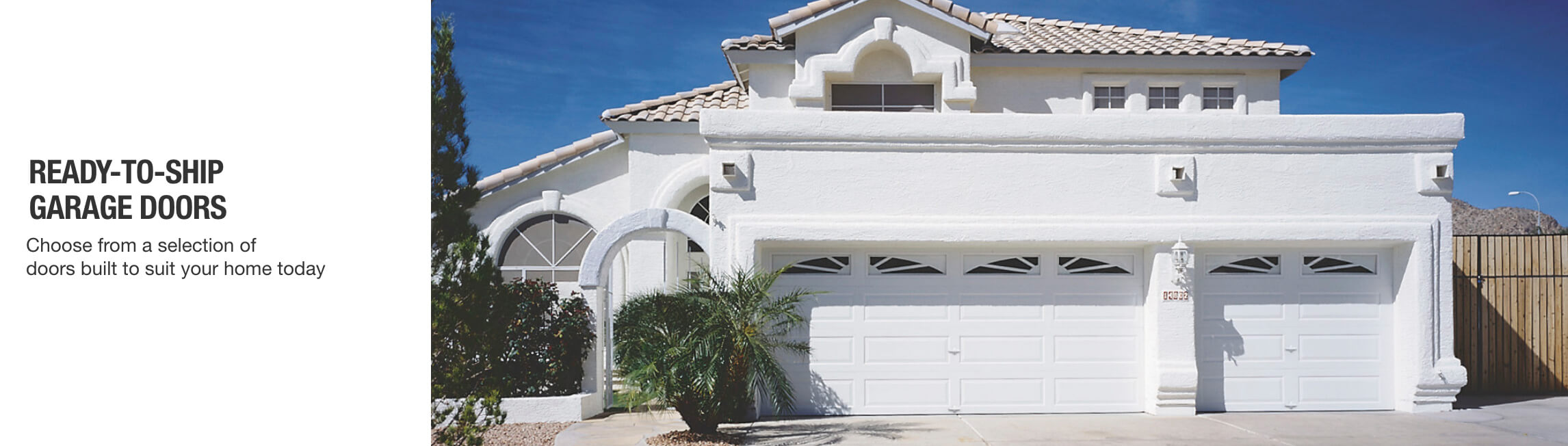 Mediterranean-style home with white garage doors and arched windows