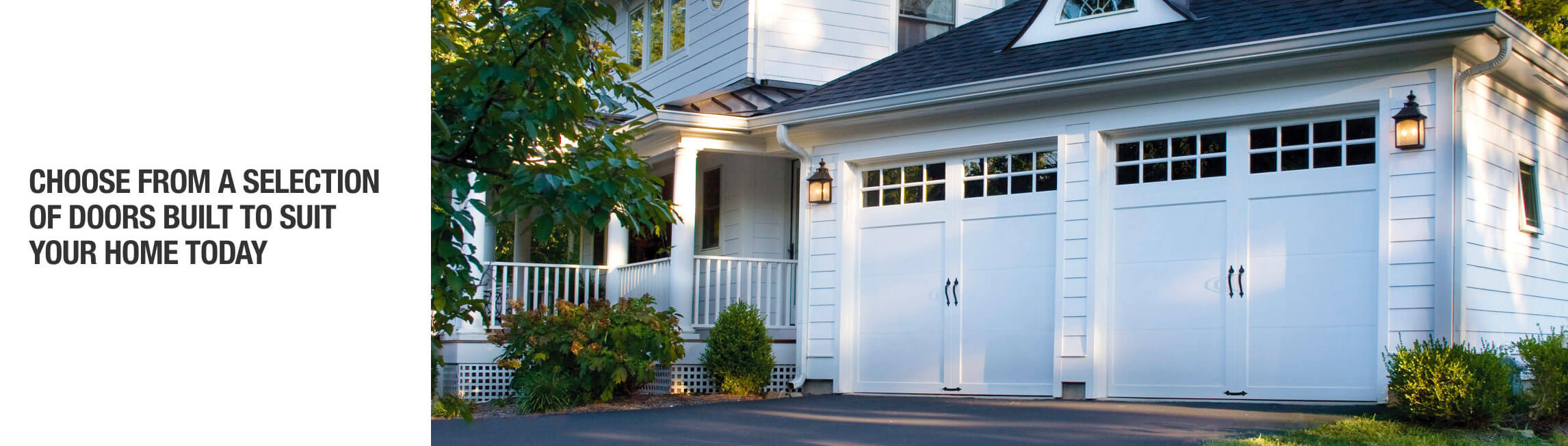 white traditional home with black roof and white siding and double white carriage style garage doors