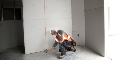 pro measuring drywall at worksite