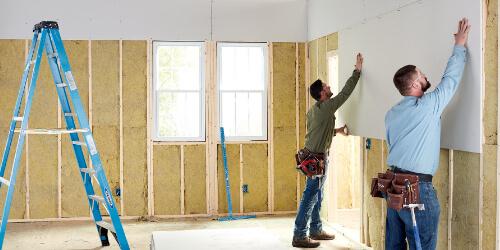 2 pros installing large drywall panel