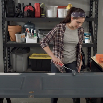 DIY woman in garage painting an interior door laying on saw horses