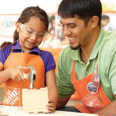 Home Depot associate helping little girl hammer a nail