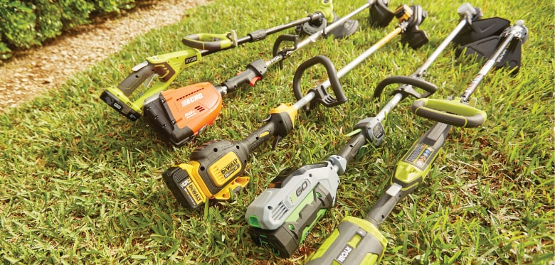 Five trimmers of different brands laying on grass